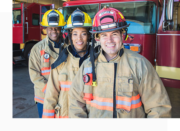 3 Firefighters standing in gear in front of firetruck - Fit for Duty Assessments concept image